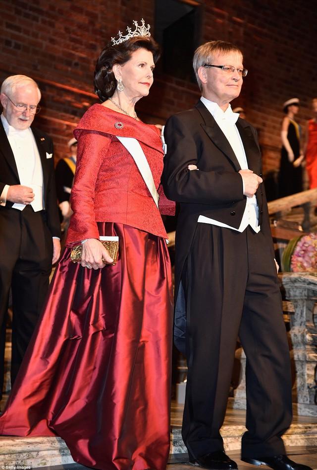 Nữ hoàng Thụy điển Sylvia lộng lẫy trong bộ váy màu đỏ. Người tháp tùng bà tại buổi lễ là Giáo sư Carl-Henrik Heldin.