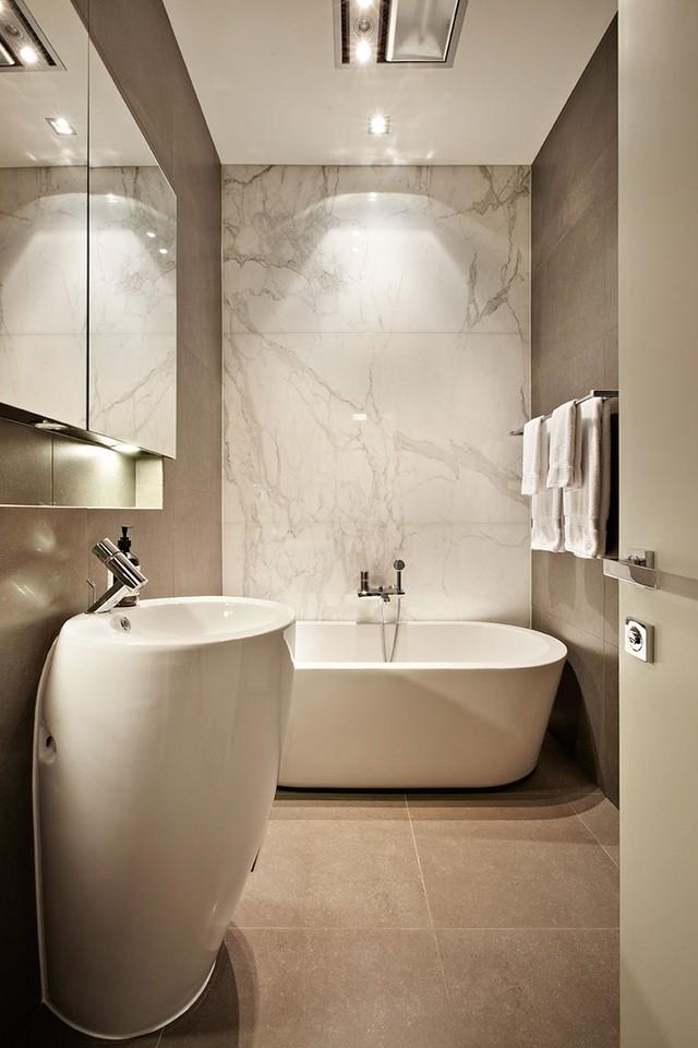 Dù có bề ngang khá hẹp nhưng các KTS đã khéo léo bài trí để biến phòng tắm này trở nên gọn gàng và hiện đại