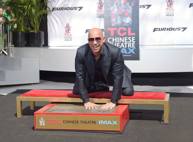 Vin Diesel in dấu tay và dấu chân mình lên xi măng trước khoảng sân nổi tiếng của TCL Chinese Theatre IMAX®