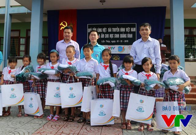 Ông Đỗ Tiến Hùng, Phó Giám đốc Quỹ Tấm lòng Việt và đại diện công ty TNHH Long Hải, công ty BHD trao áo ấm cho học sinh trường Tiểu học Lộc Thủy