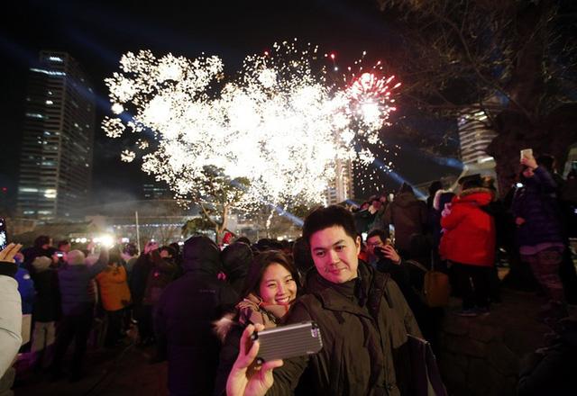 Một cặp tình nhân Hàn Quốc chụp ảnh với pháo hoa tại thủ đô Seoul