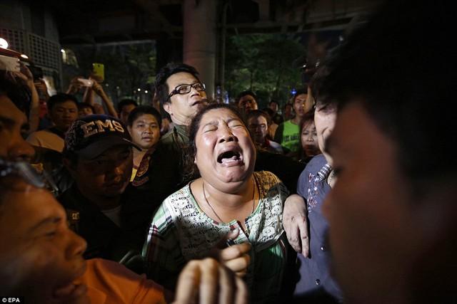 Một người phụ nữ đau đớn tìm kiếm người thân bị mất tích sau vụ nổ.