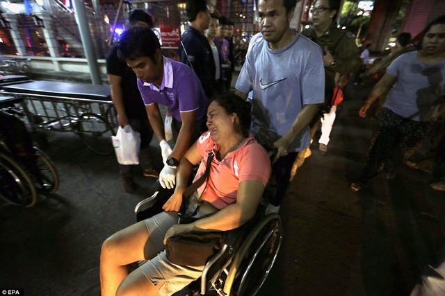 Một người phụ nữ hoảng sợ, được đẩy ra ngoài hiện trường bằng xe lăn.