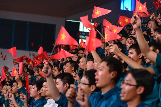 Hơn 700 chiến sĩ cũng giơ cao hình ảnh cờ đỏ sao vàng và hòa theo lời ca của ca khúc này.
