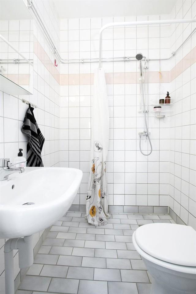 Phòng tắm cũng mang màu trắng chủ đạo nhưng có điểm nhấn là màu sắc ở khăn tắm, khăn lau và rèm che.