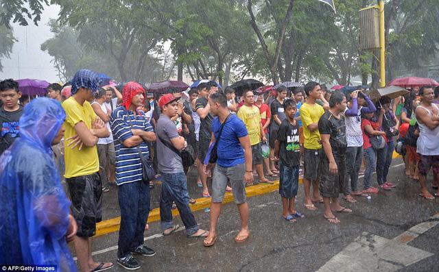 Cơn mưa rào ập đến không ngăn được những CĐV nhiệt thành nán lại cổ vũ.