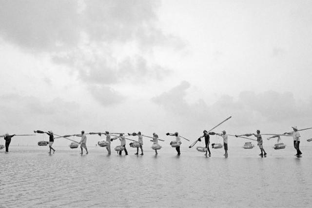 Gánh sản phẩm đánh bắt được trên bờ biển sau khi thủy triều rút, Bạc Liêu, Việt Nam - tác phẩm đoạt giải Khuyến khích - Ảnh: Phuc Ngo Quang