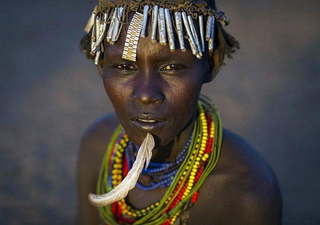 Một người đàn ông của bộ lạc với dây đeo đồng hồ, vòng cổ và lông chim