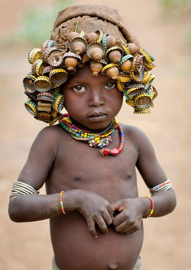 Một em bé bộ lạc Daasanach với chiếc mũ nắp chai đặc trưng.