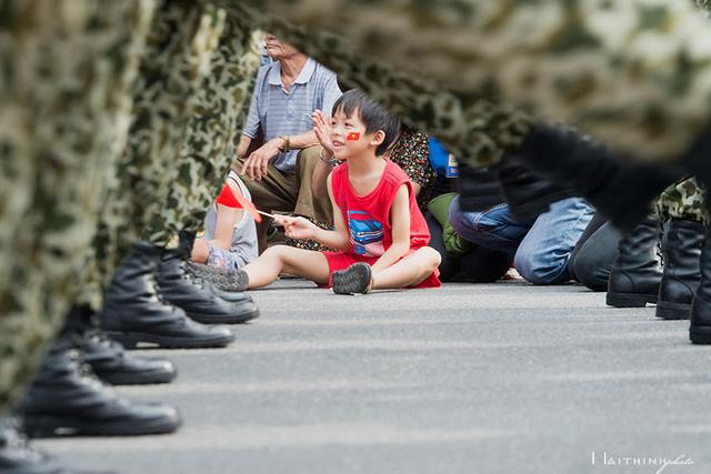 Một em nhỏ thích thú khi theo dõi những nhịp bước đều đặn của các thành viên đoàn diễu binh.