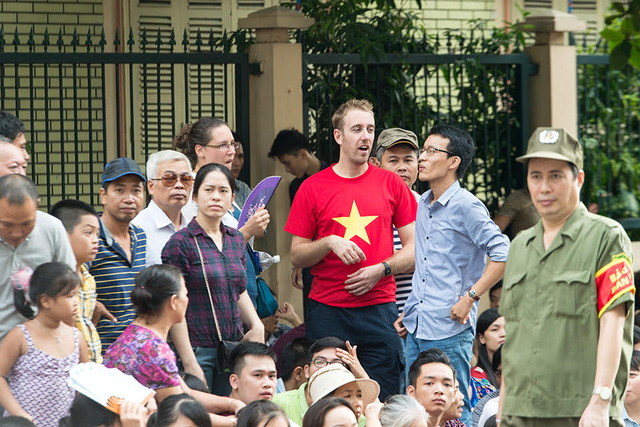 Du khách nước ngoài cũng tới xem buổi lễ với áo cờ đỏ sao vàng.