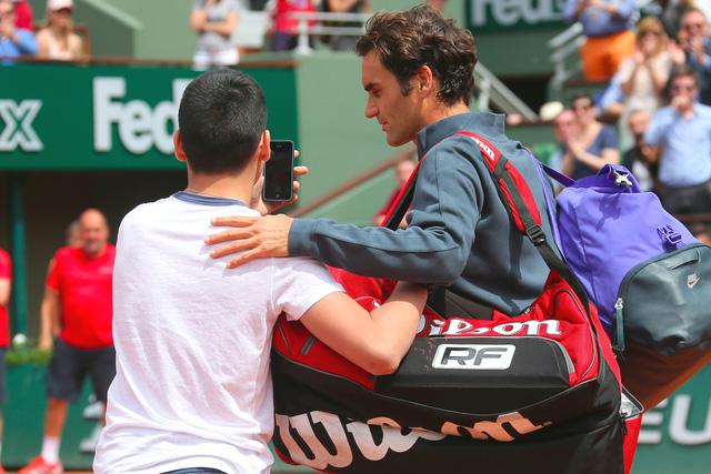 Một cậu bé vượt qua hàng rào bảo vệ, xuống sân và cố gắng chụp ảnh selfie với Federer.