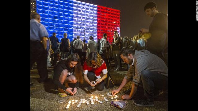 Người dân thắp nến xếp thành chữ Paris tại Quảng trường Rabin (Israel). Tòa nhà được thắp sáng màu quốc kỳ Pháp phía sau chính là văn phòng chính quyền thành phố Tel Aviv.