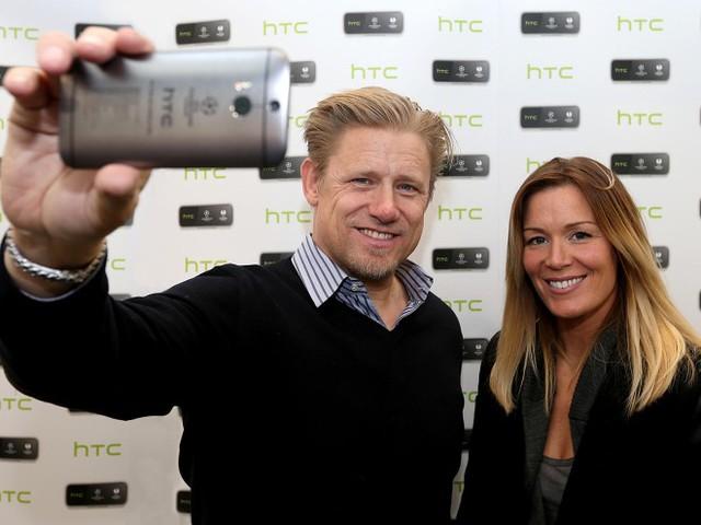 Peter Schmeichel của Manchester United và thủ môn Emma Byrne của đội bóng nữ Arsenal chụp ảnh tự sướng bằng chiếc HTC One M8 phiên bản đặc biệt