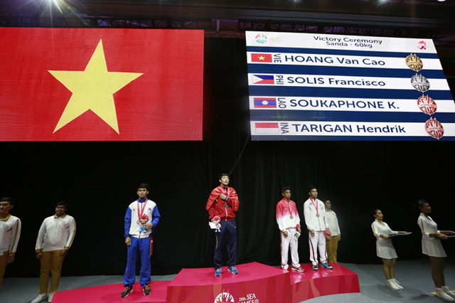 Hoàng Văn Cao (áo đỏ, đứng giữa) đã xuất sắc mang về tấm HCV Wushu Sandao ở hạng cân 60kg cho đoàn thể thao Việt Nam tại SEA Games 28.