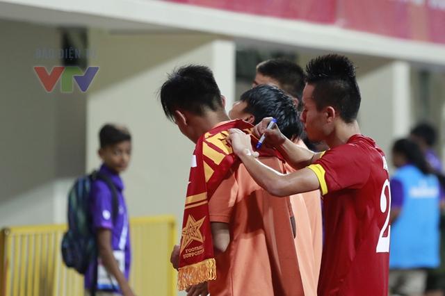 Huy Toàn (phải) mượn lưng đồng đội để ký tặng người hâm mộ.