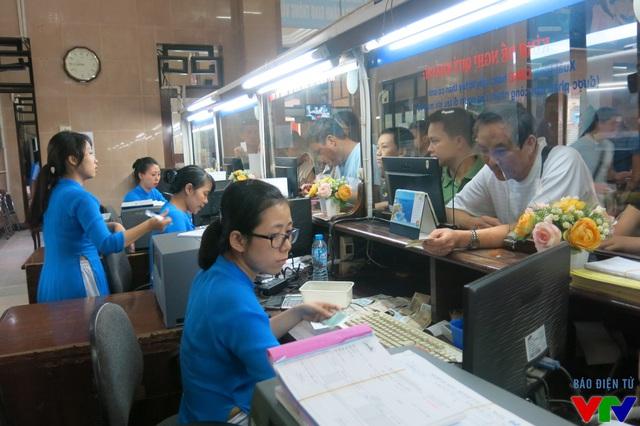 Nhân viên quầy vé làm thủ tục cho hành khách với hệ thống mới