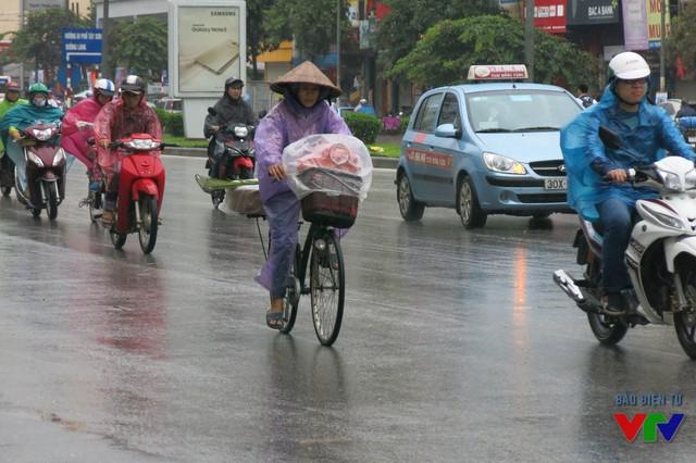 Nhiều người dân Hà Nội đi đường vào chiều nay cảm nhận rõ rệt thời tiết se lạnh kèm theo mưa gió
