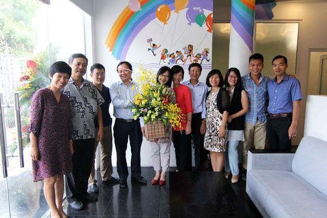 Nhà báo Nhật Hoa (đứng giữa) nhận lẵng hoa chúc mừng từ nhà báo Đỗ Quốc Khánh - Trưởng Ban Khoa giáo (thứ 4 từ trái sang), và nhà báo Nguyễn Hoàng Lâm, Phó Trưởng Ban Khoa giáo (thứ 3 từ trái sang).