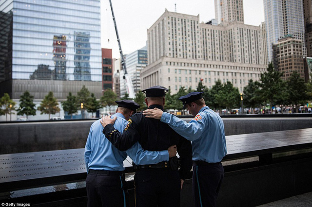 From left to right: Zachary Ellicott, a firefighter in Stanhope, NJ, Mitch Ellicott, a lieutenant with the Sussex County Sherrifs office and father to Zach and Benjamin, and Benjamin Ellicott, a firefighter in Stanhope, NJ, take a moment to remember a family member lost in the terrorist attack of September 11, 2001, on Friday in New York City
