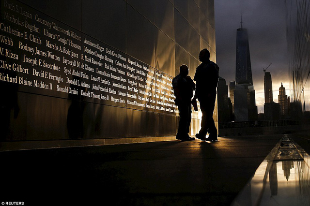 People read the victims names of the 9/11 Empty Sky memorial at sunrise across from New Yorks Lower Manhattan and One World Trade Center, in Liberty State Park in Jersey City, New Jersey, September 11, 2015