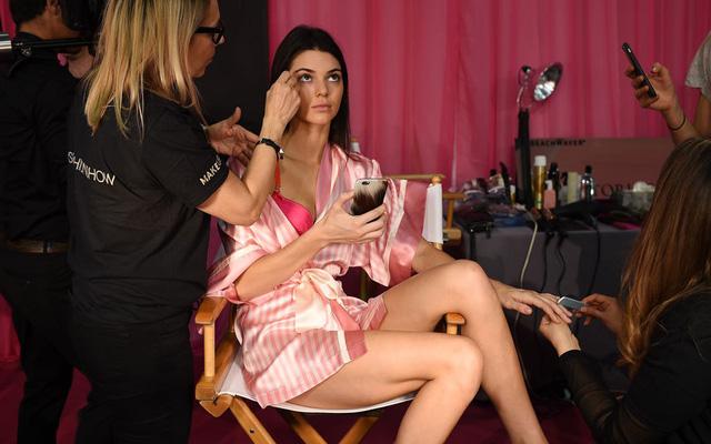 Đang được trang điểm song Kendall Jenner vẫn không quên kiểm tra điện thoại.