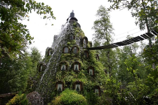 Khách sạn Montana Magica Lodge ở Chile có kiến trúc độc đáo hình tháp, với cây cối phủ xung quanh và nước chảy từ đỉnh tòa nhà xuống.