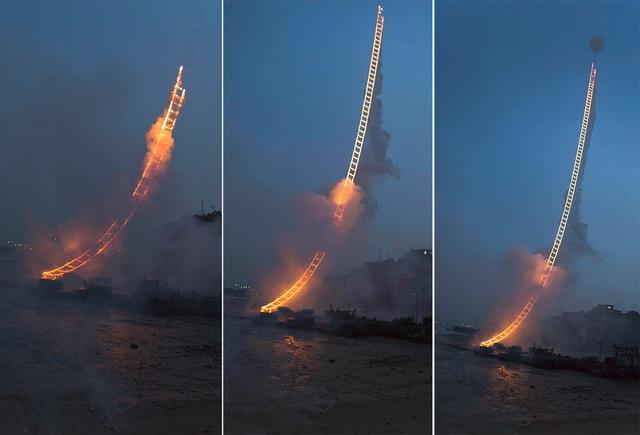 Pháo bông cháy dần trên thang, khiến chiếc thang sáng rực giữa bầu trời