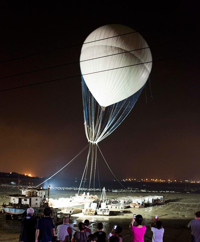 Để nâng chiếc thang lên trên cao, nghệ nhân Cai Guo-Qiang đã sử dụng một khinh khí cầu lớn
