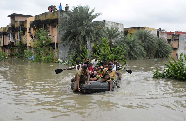 Nhân viên cứu hộ và cảnh sát hỗ trợ giúp đỡ người dân trong vùng bị ngập nước.