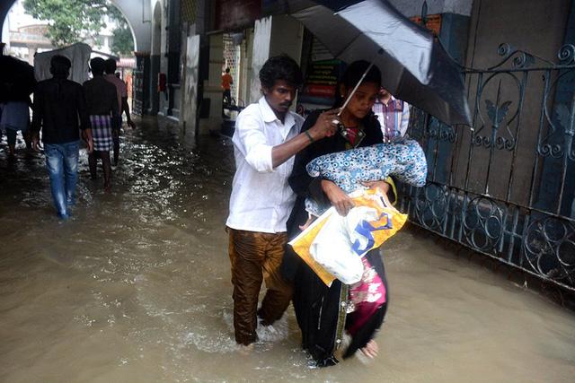 Đôi vợ chồng bế con đi trong nước lũ ở bệnh viện Egmore, Chennai.