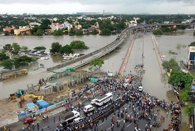 Mọi người chứng kiến cảnh nước lũ tràn qua đường cao tốc ở Chennai.