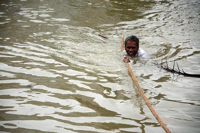 Một người dân dùng dây để vượt nước lũ.
