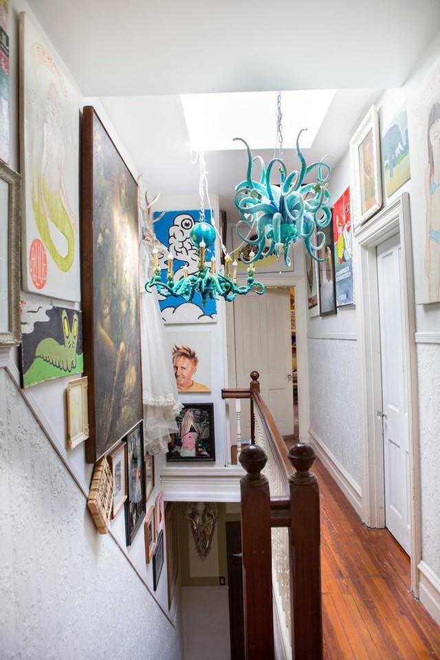 Góc hành lang tầng 2 của ngôi nhà được trang trí bằng nhiều tranh, ảnh và đèn bạch tuộc xanh.