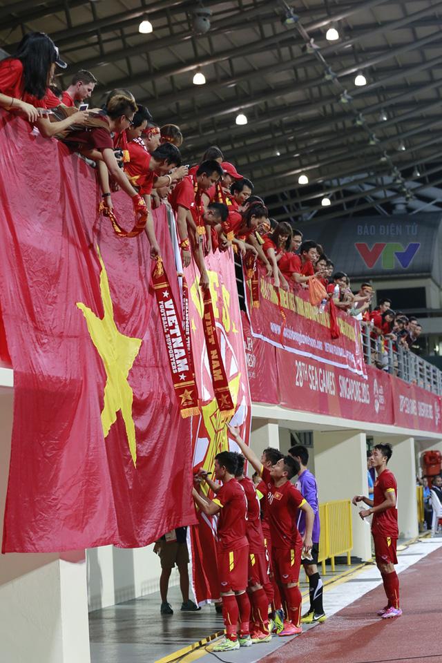 Người hâm mộ đưa những chiếc khăn cổ vũ xuống để các cầu thủ ký tặng.