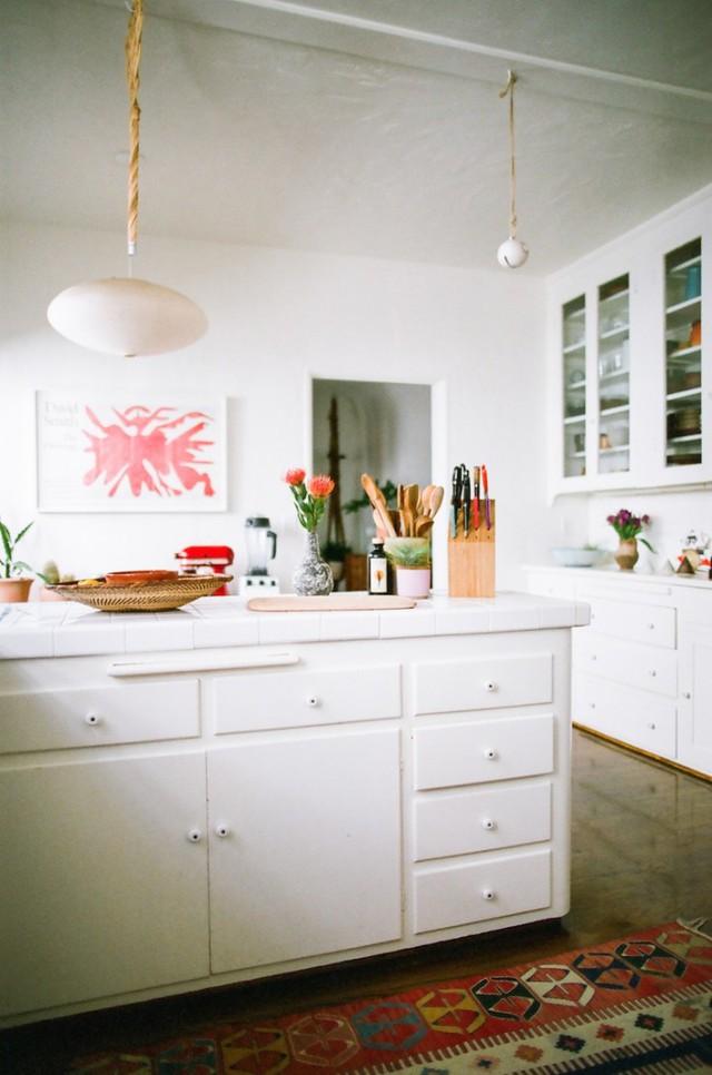 Góc bếp cũng mang tông màu trắng chủ đạo, nhưng màu sắc ở các vật dụng trở thành điểm nhấn.