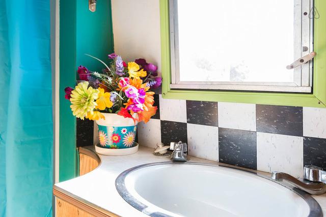 Lọ hoa xinh xắn nhiều màu sắc được đặt trong phòng tắm.
