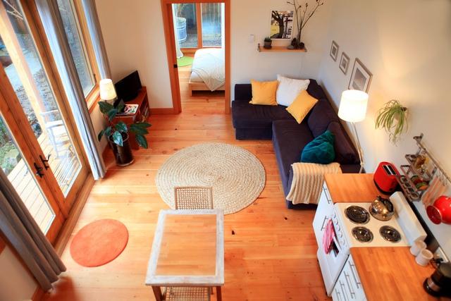 Căn nhà mang không gian mở, với cửa kính lớn và tận dụng chung phòng khách với bếp.