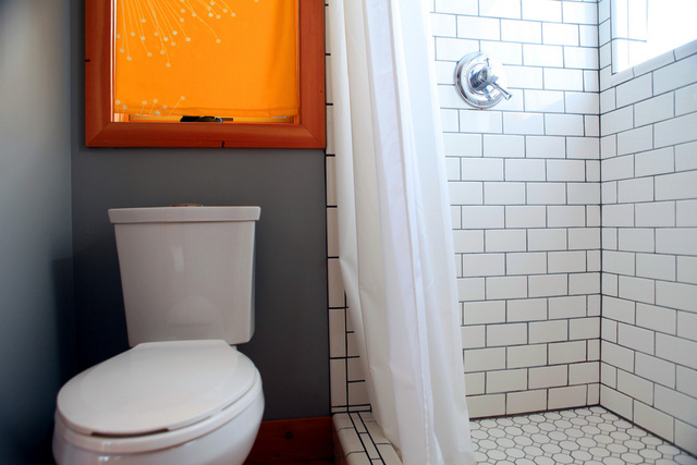 Phòng tắm mang tông màu trắng - xám, có tranh treo màu cam làm điểm nhấn.
