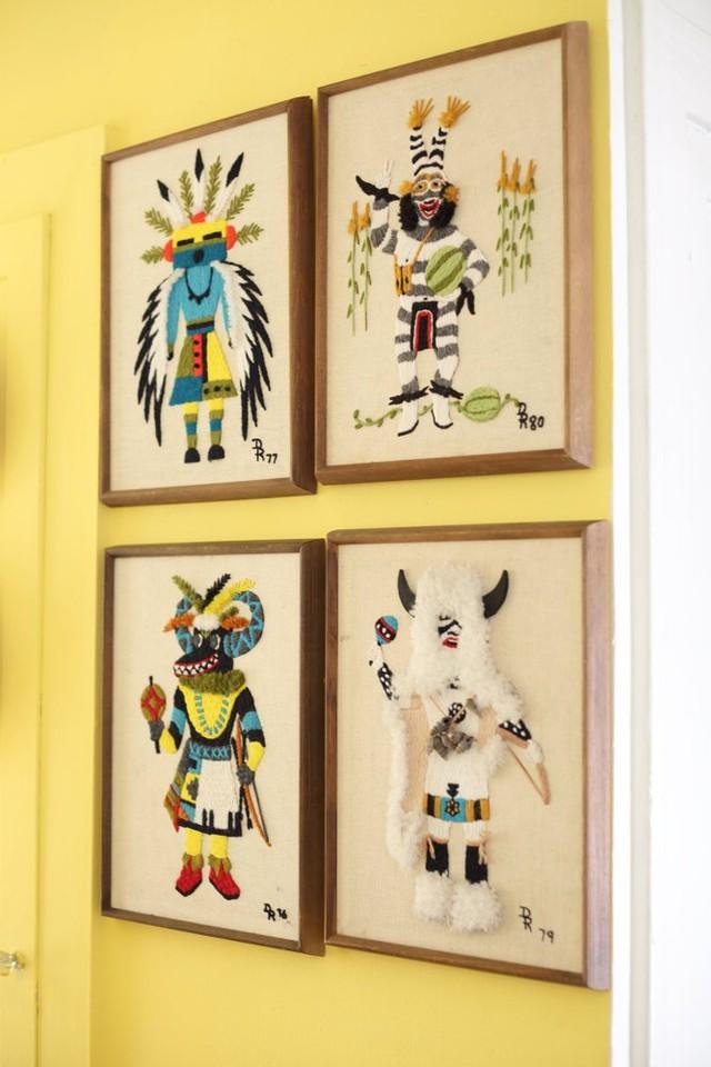Những bức tranh thêu với màu sắc, hình họa rực rỡ được treo ở góc tường màu nắng này.
