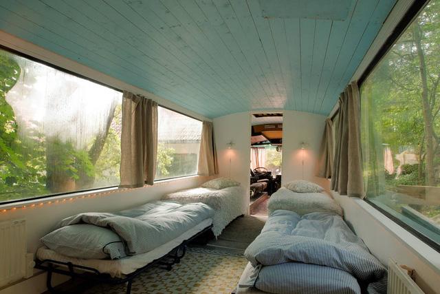 Phòng khách và phòng ngủ được ngăn cách nhau bằng mảng tường trắng có lối ra vào.
