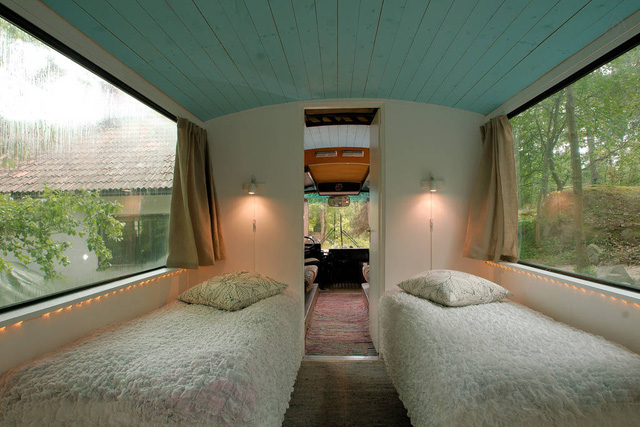 Phòng ngủ đơn giản với giường kê hai bên và rèm cửa.