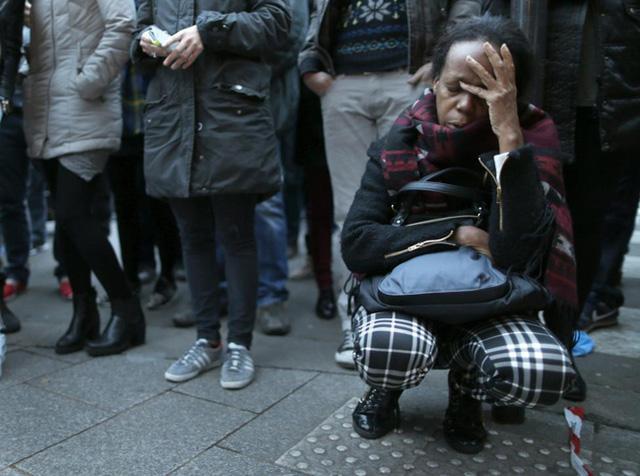 Một người phụ nữ thể hiện tình cảm của cô tại nơi xảy ra vụ tấn công kinh hoàng. (Ảnh: Reuters)