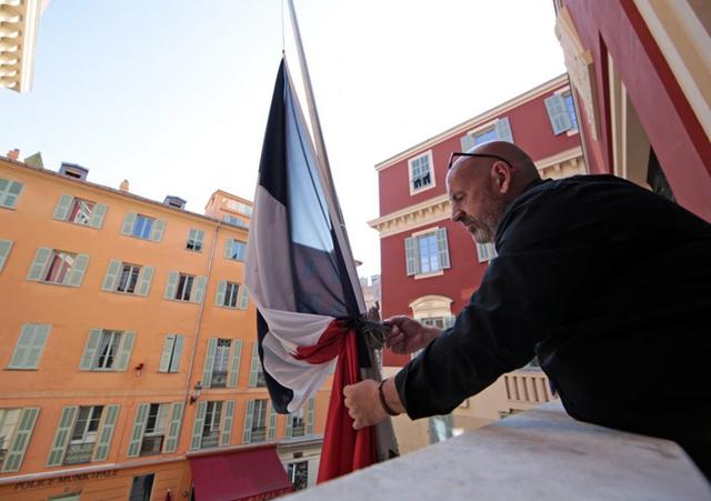 Một nhân viên của thành phố gắn một dải ruy băng màu đen xung quanh lá cờ Pháp. Đây là dấu hiệu để tang cho các nạn nhân một ngày sau khi một loạt các vụ nổ súng chết người ở Paris. (Ảnh: REUTERS / Eric Gaillard)