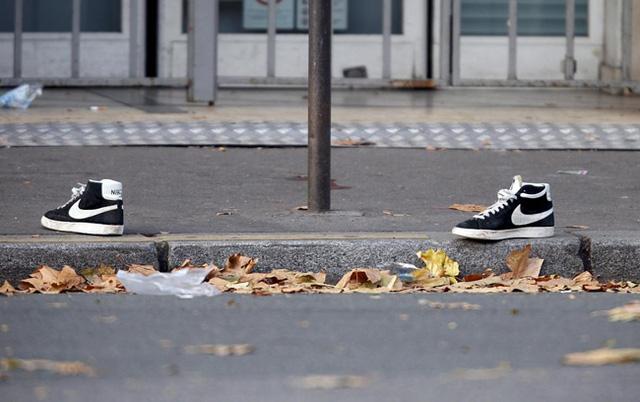 Một đôi giày bị bỏ rơi trên đường phố gần phòng hòa nhạc Bataclan. (Ảnh: REUTERS / Charles Plat)