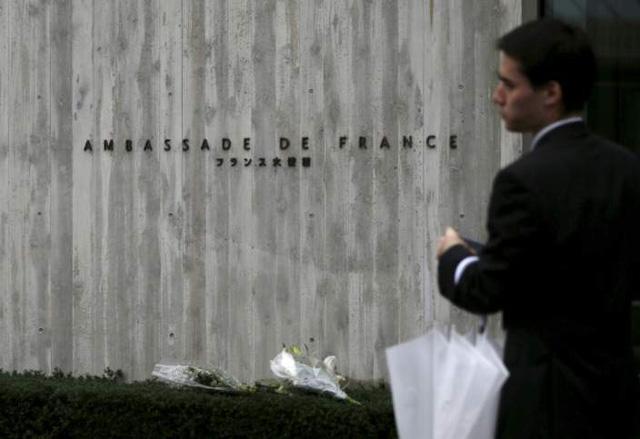 Một người đàn ông đặt một bó hoa bên ngoài ĐSQ Pháp tại thủ đô Tokyo, Nhật Bản.