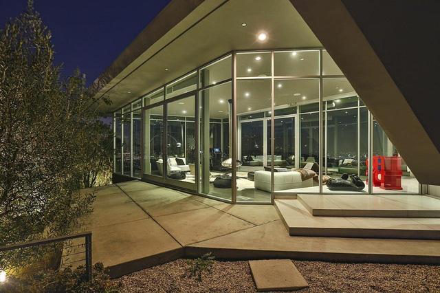Căn nhà được bao quanh bởi lớp cửa kính trong, giúp không gian được đón ánh sáng tự nhiên.