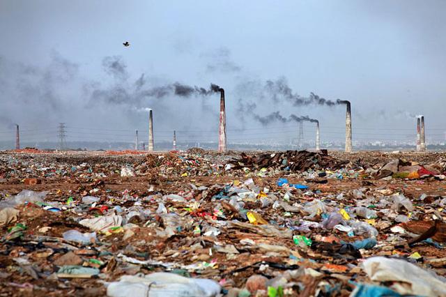 Quang cảnh bãi rác thải rộng lớn bên những ống khói công nghiệp ở Bangladesh.