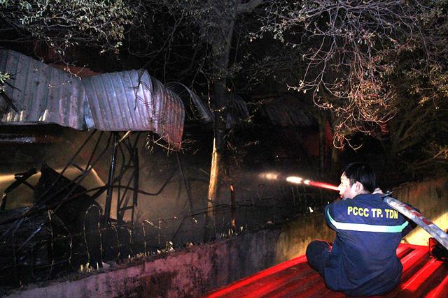 Lính cứu hỏa dùng vòi rồng phun nước dập lửa từ bên ngoài.