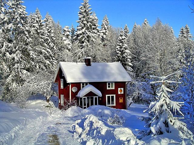 Một căn nhà sơn màu đỏ nội bật giữa lớp tuyết trắng tại Thụy Điển